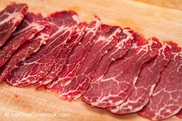 Thinly Sliced Meat on a cutting board.