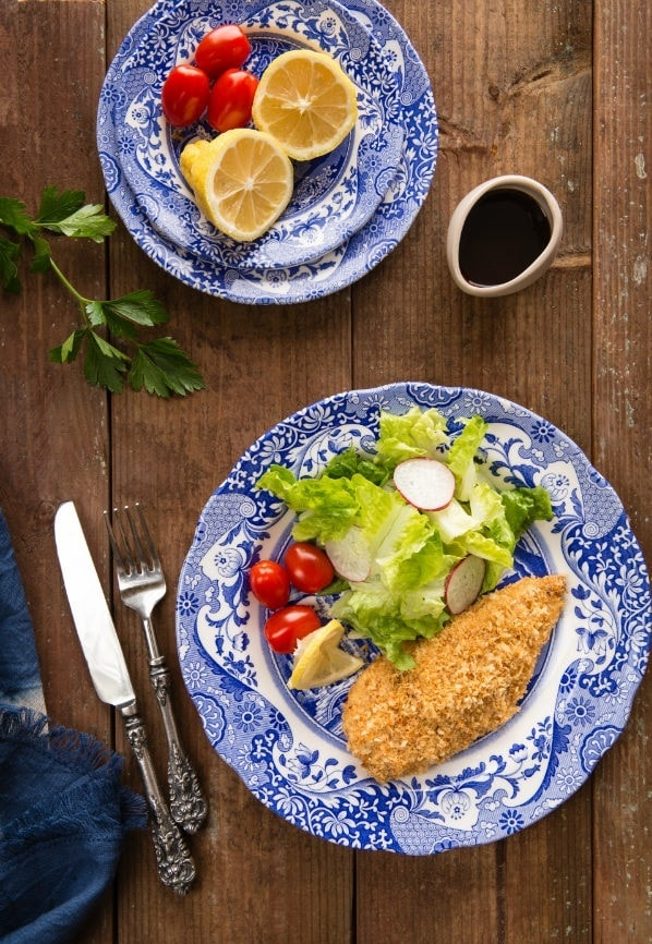 Baked Chicken Katsu and spring salad on plates.