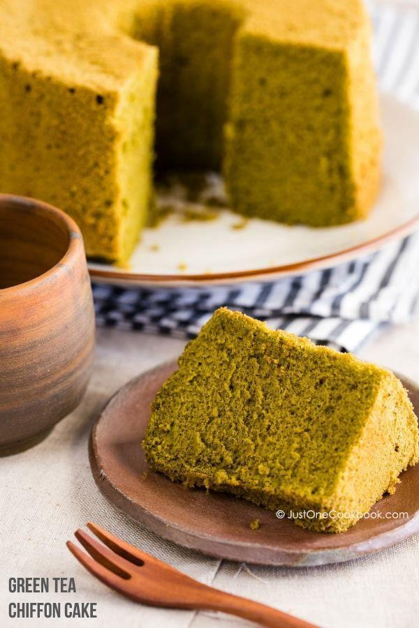 Sliced Green Tea Chiffon Cake on small plate and whole chiffon cake in the back.