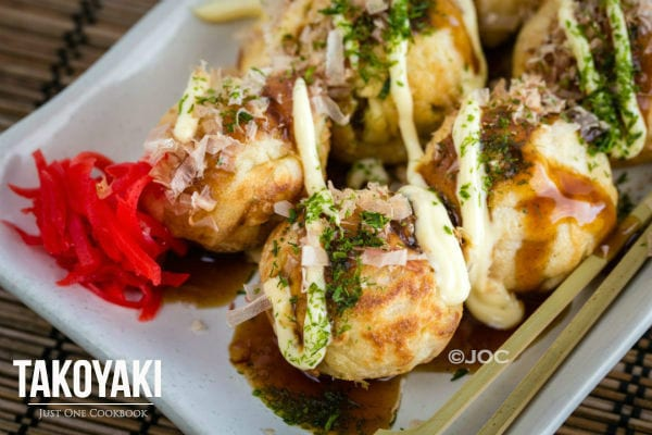 Takoyaki with Takoyaki sauce and mayo on a plate.