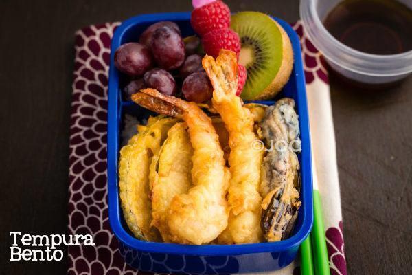 Tempura Bento with tempura, rice and fruits on a table.