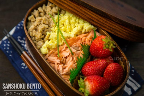 Sanshoku Bento with strawberry on a table.