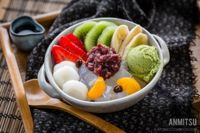 Anmitsu with green tea ice cream, shiratamadango, anko, and fruit in a bowl.