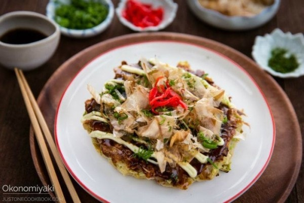 Okonomiyaki on a white plate and topping in a little dishes.