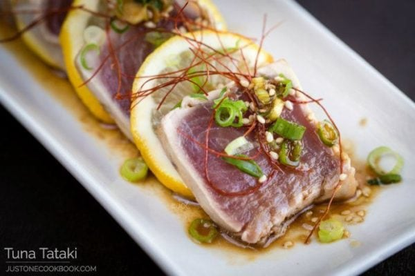 Tuna Tataki and sliced lemons on a plate.
