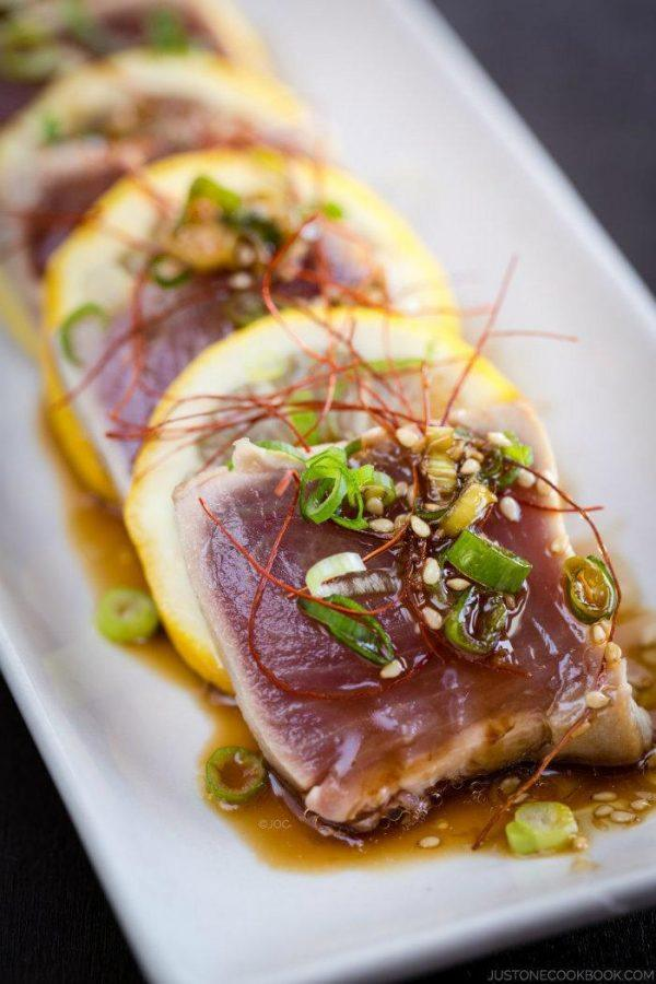 Tuna Tataki and sliced lemons on a white plate.