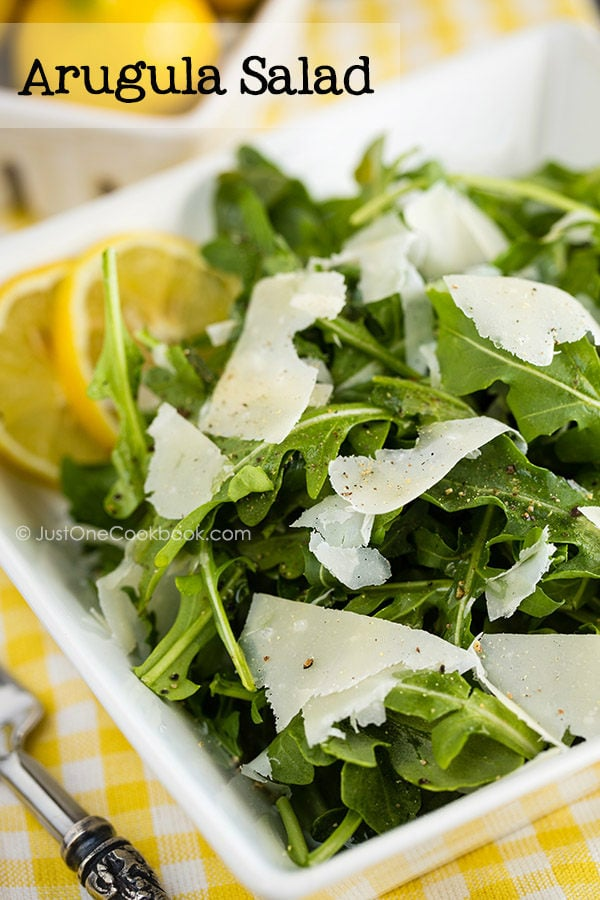 Arugula Salad with shaved Parmesan cheese in a white dish.