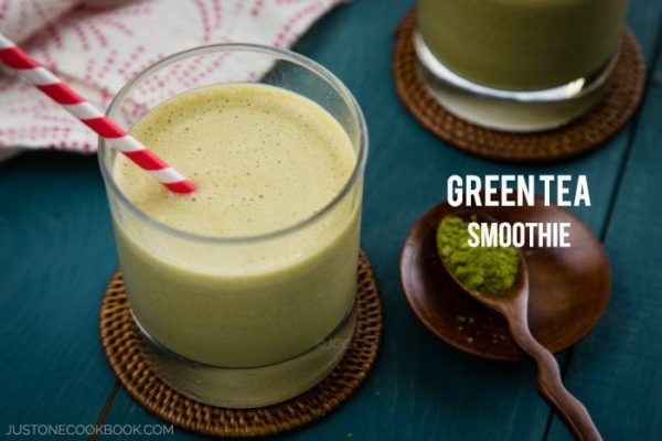 Green Tea Smoothie in a glass with teaspoon of green tea powder on a table.