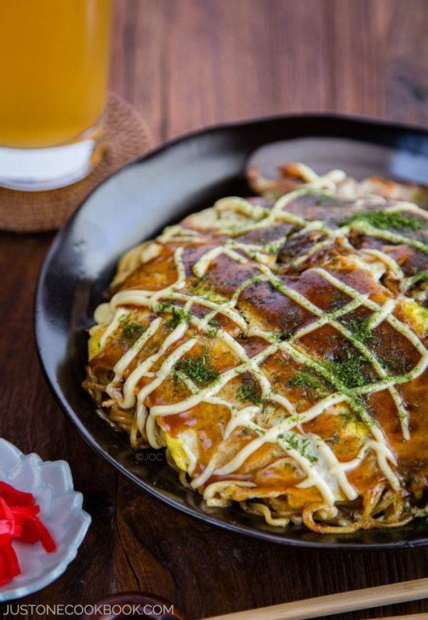 Hiroshimayaki, Hiroshima Style Okonomiyaki on a black plate and glass of drink on a wooden table.