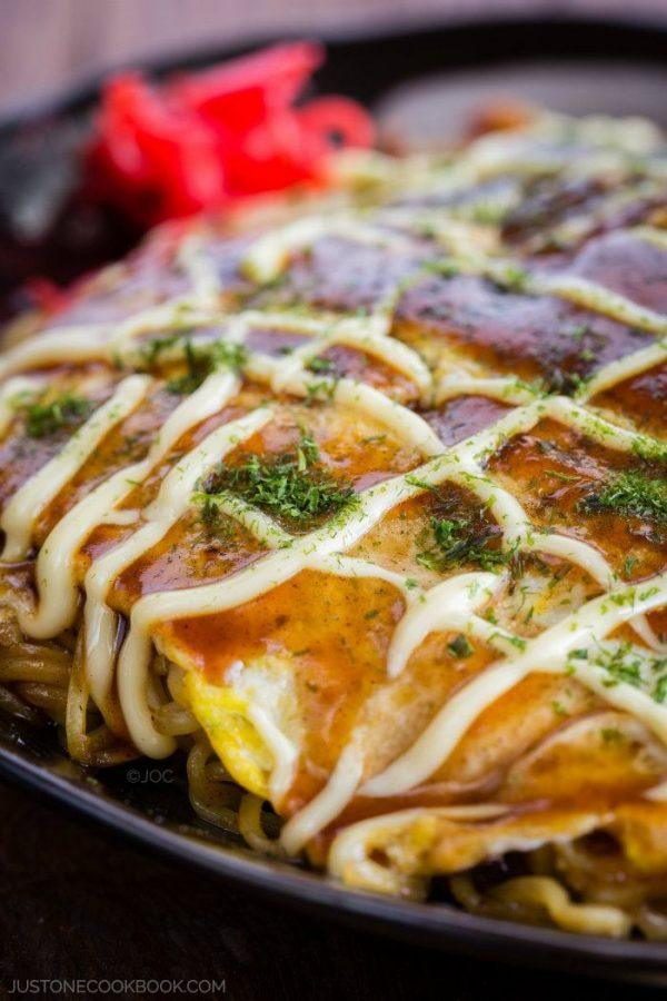 Hiroshimayaki, Hiroshima Style Okonomiyaki on a black plate with red pickled ginger.