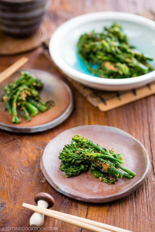Broccolini Gomaae in small dishes on the wooden table.