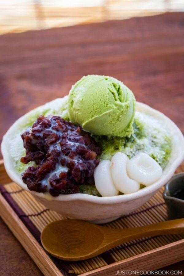 Green Tea Shaved Ice with sweet red bean, matcha green tea ice cream and shiratama dango in a bowl.