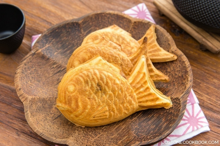 Taiyaki, Japanese fish-shaped cake snack with sweet red bean filling on a wooden plate.