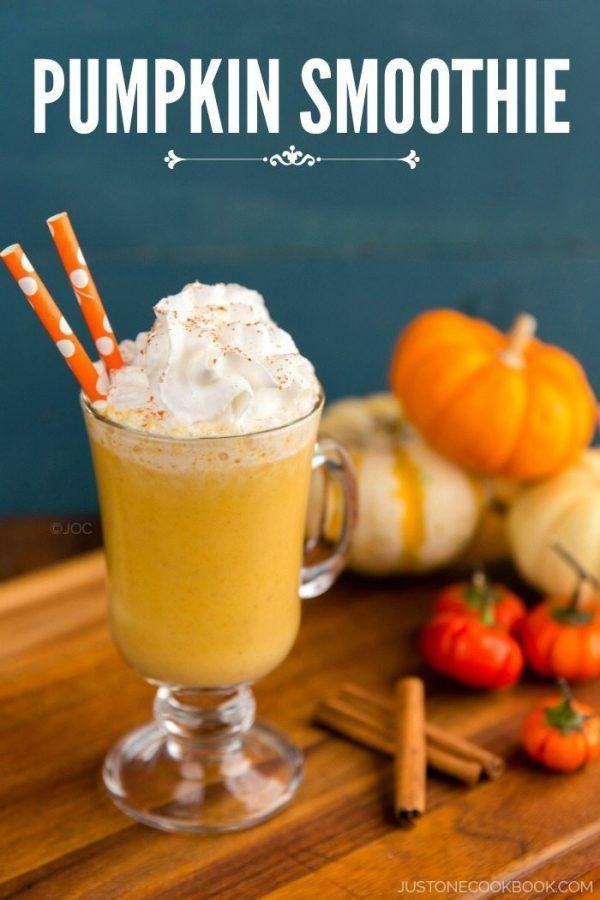 Pumpkin smoothie in a glass with whipped cream on top.