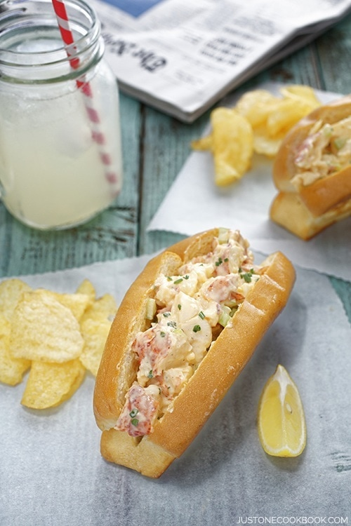 Lobster Roll, chips and a glass of lemonade on a wooden table.