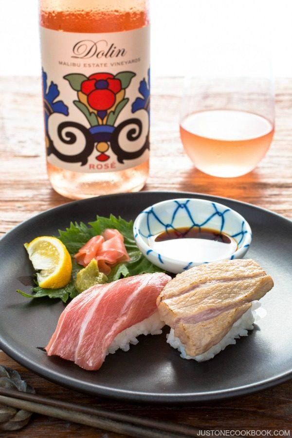 Otoro Sushi on a plate and bottle of drink with glass.