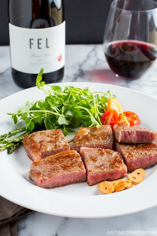 Wagyu beef steak and salad on a white plate and a bottle and glass of wine.
