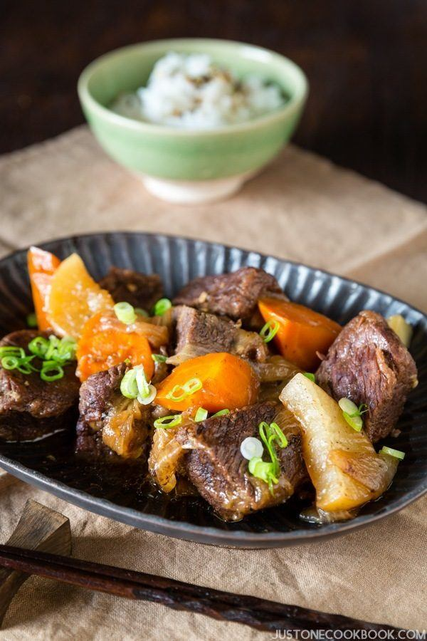 Pressure Cooker Short Ribs on a plate and a bowl of rice.
