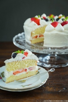 A sliced of Strawberry Shortcake on a small plate and whole cake on a glass cake stand in the back.