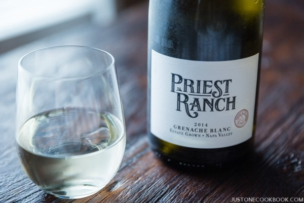 priest ranch grenache blanc in a bottle and a glass.