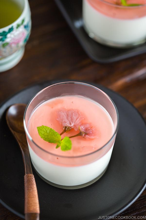 Cherry Blossom Milk Pudding in a glass cup served with green tea.