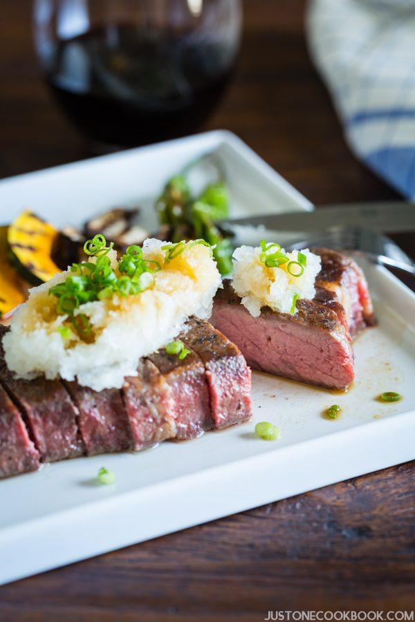 Sous Vide beef steak with grated daikon, scallion and ponzu sauce on the white plate.