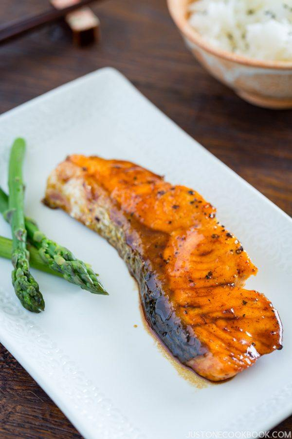 Teriyaki Salmon and steamed asparagus on a white plate.