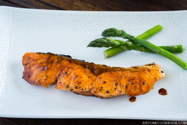 Teriyaki Salmon and steamed asparagus on the white plate.