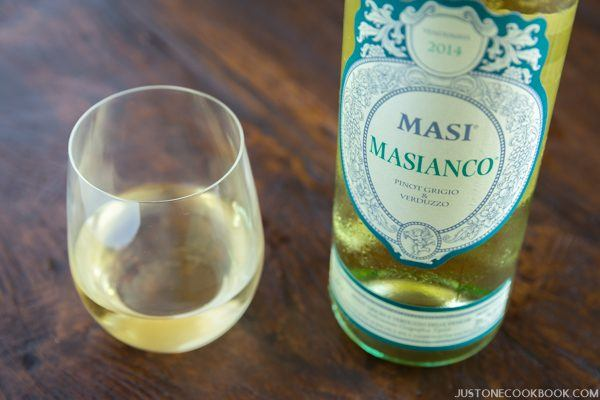 A bottle of MASI MASIANCO and a glass on the wooden table.