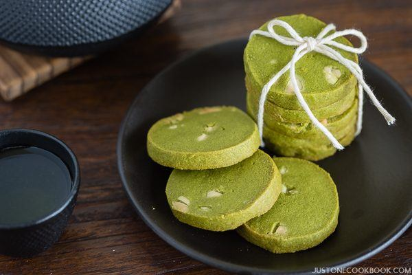 Green Tea Cookies on a black plate and a cup of tea.