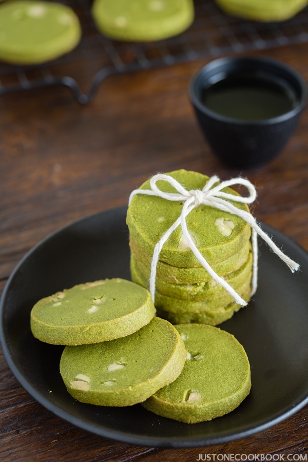 Green Tea Cookies on the black plate and cup of tea.