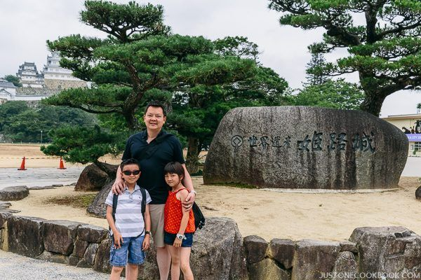A man with two children standing next to a rock at Himeji Castle