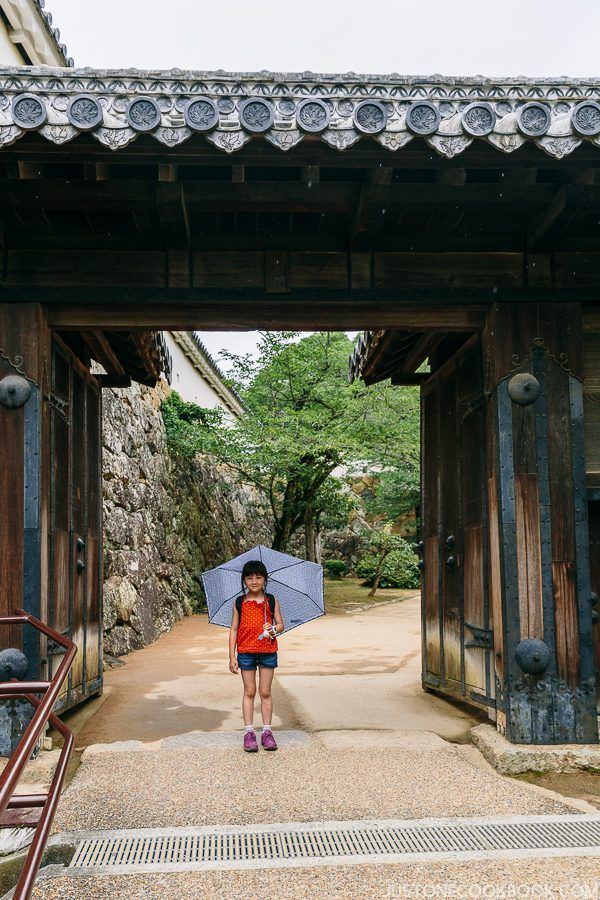 a girl standing under a wood gate