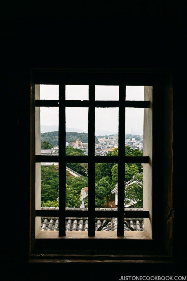 view of the surrounding area through a window in himeji castle
