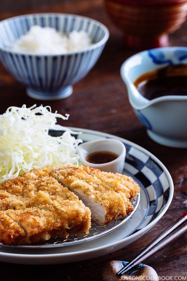 Miso Katsu on a plate with miso sauce and a bowl of rice.