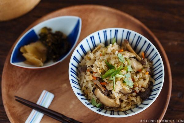 Takikomi Gohan in a rice bowl and a small bowl of pickled on the wooden tray.