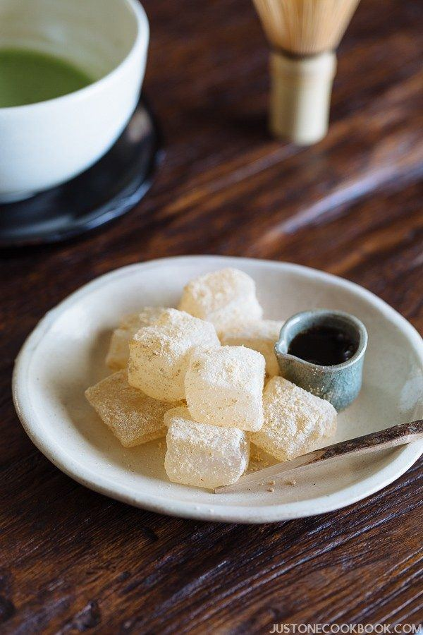 Warabi Mochi and Kuromitsu syrup on a white plate and green tea on the wooden table.