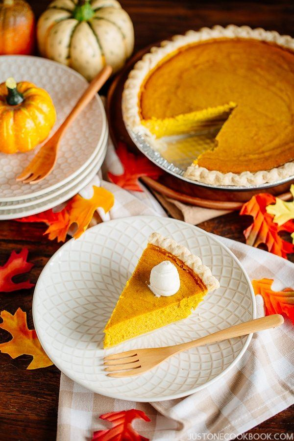 Kabocha Squash Pie with whipped cream on a small plate and pumpkins on a table.