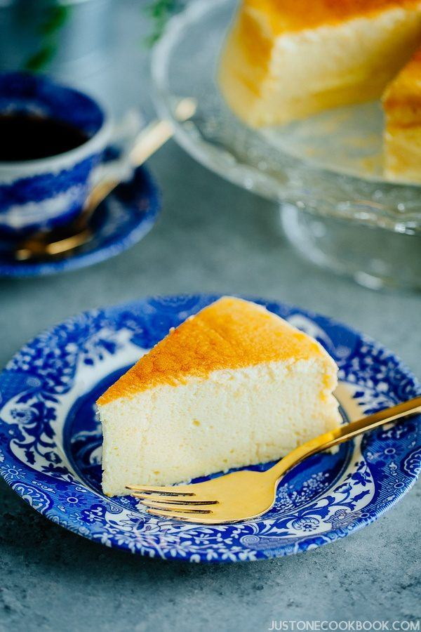 Sliced Japanese Cheesecake on blue plate with gold fork and tea cup on the back.