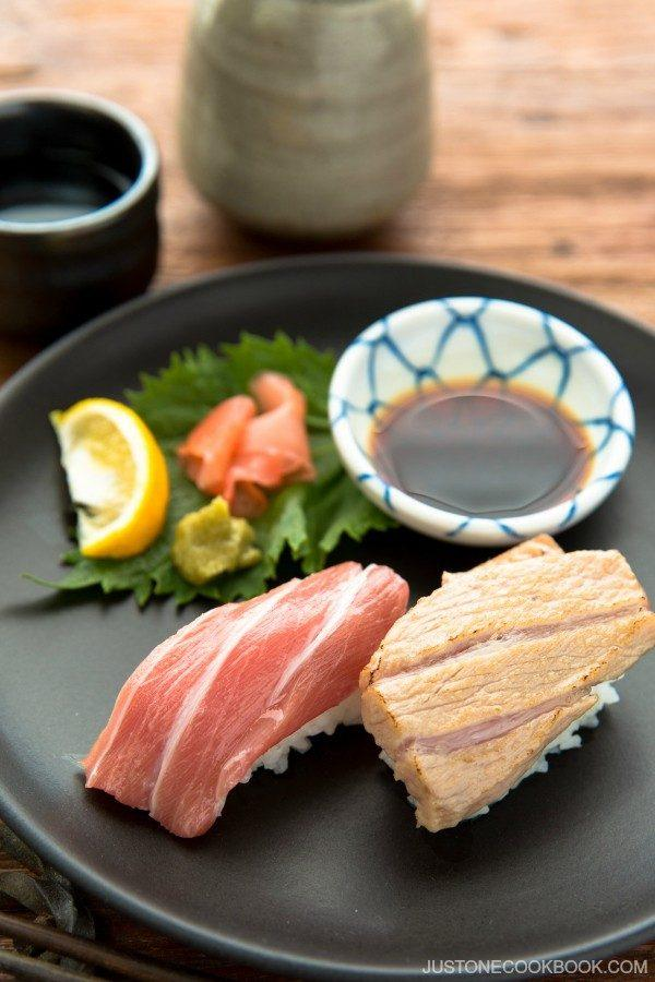 Otoro Sushi on a plate with soy sauce and garnish.