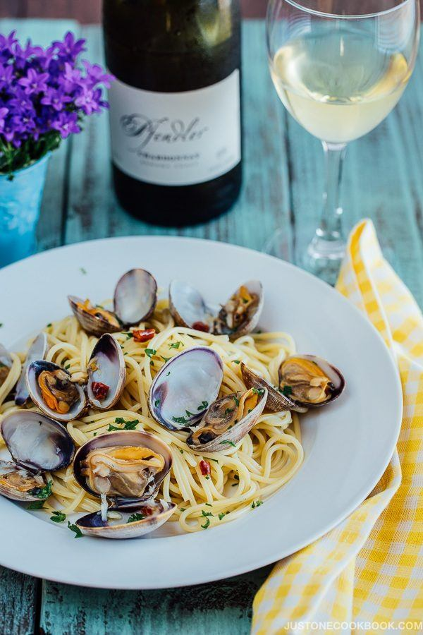 Clam Pasta on a plate with a bottle and a glass of wine on wooden table.