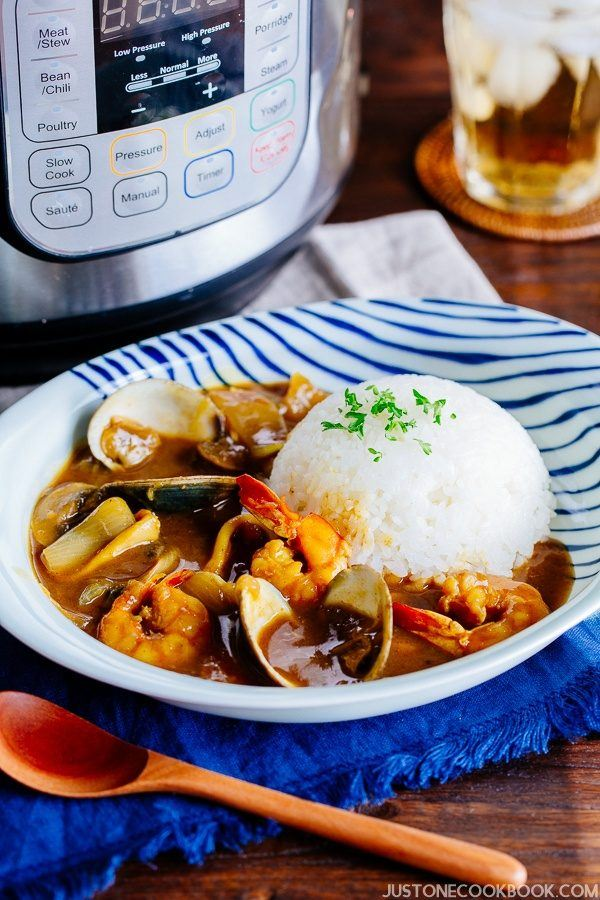 Pressure Cooker Japanese Seafood Curry with white rice on a plate and pressure cooker on the wooden table.