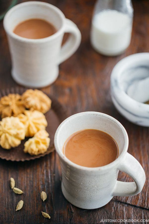 Masala Chai in cups and a plate of cookies.