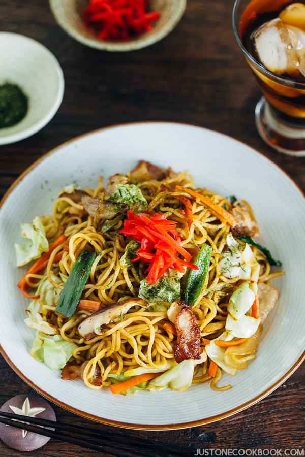 Yakisoba on a plate topped with pickled red ginger.