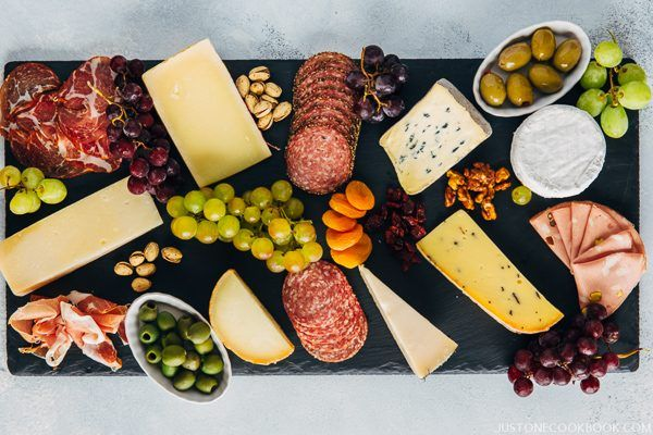 Cheese Board with olives, crackers, salami and grapes.