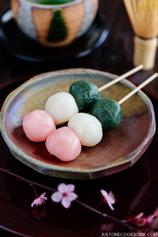 Hanami Dango on a small plate and cup of green tea.