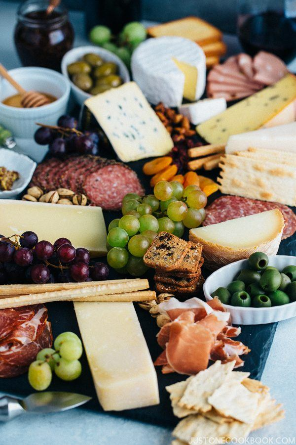 Cheese Board with grapes, olives, slices of meat and cacklers.
