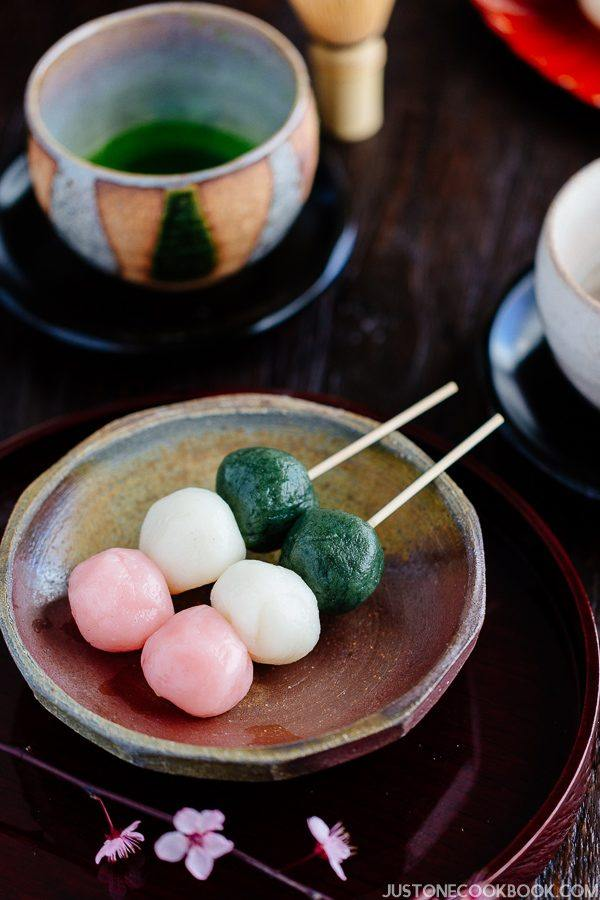 Hanami Dango on a plate with cup of green tea.