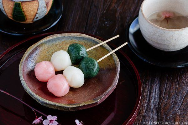 Hanami Dango on a small plate with cup of tea.