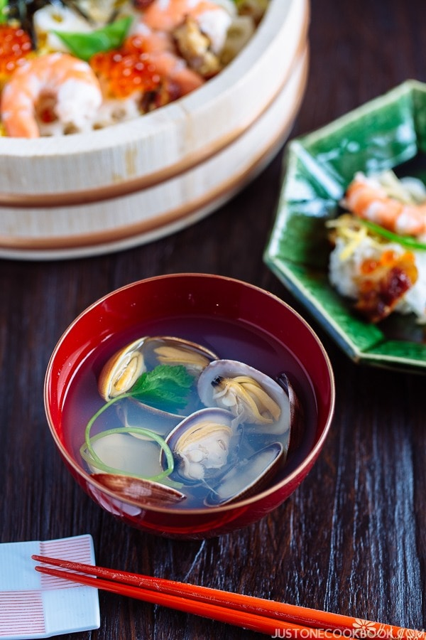 Japanese Clam Soup with Clear Broth in a red bowl and sushi in a wooden tray.